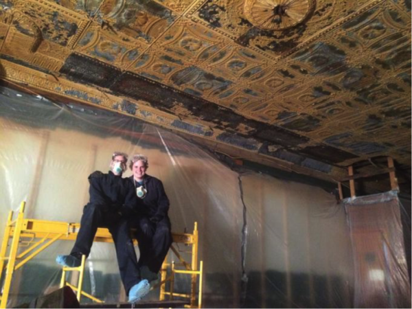 Hands on crew members inside the Sunshine building doing restoration work to the punched tin ceiling. Photo courtesy of Alex Thomas.