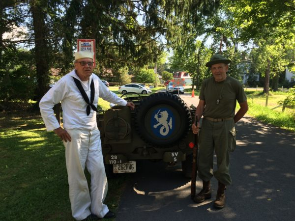Daniel and Bill with a Jeep that has the logo of the 59th Coastal Artillery unit painted on the back